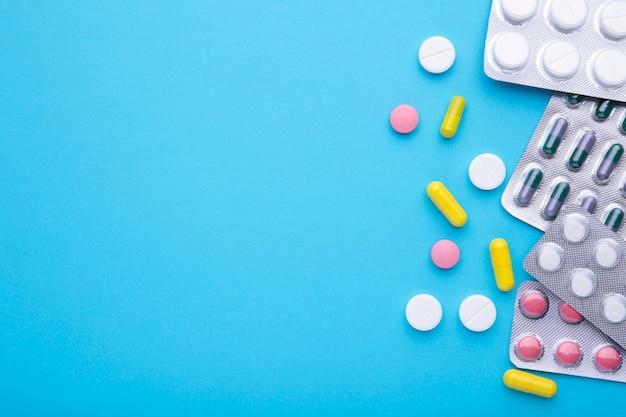 Pílulas coloridas e comprimidos em blister azul