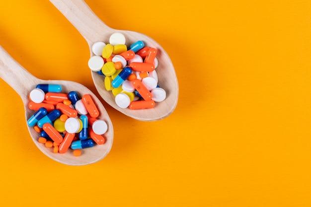 Pílulas coloridas em colheres de madeira
