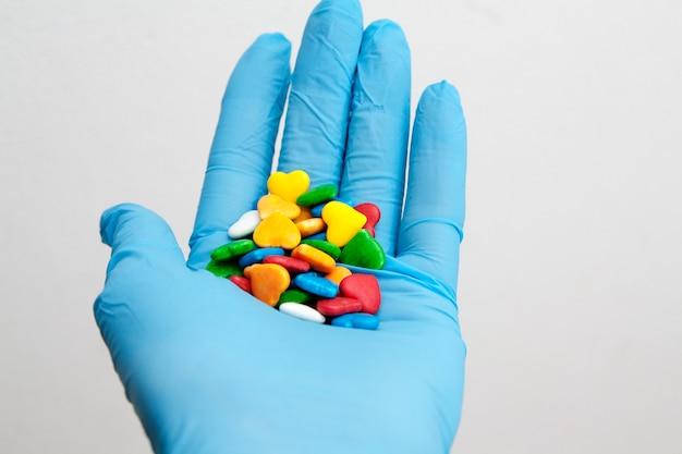 Pílulas coloridas em forma de um coração em uma mão enluvada. conceito de cuidados médicos