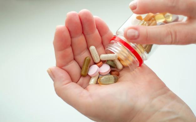 Pílulas coloridas, vitaminas de diferentes grupos, como vitaminas a, b, c, e, d, luteína + mirtilos, beta-karatina + espinheiro, óleo de tomilho preto, omega 3 na palma da mão.