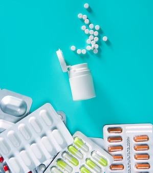 Pílulas de bolha prata sobre garrafa aberta de verde branco medica