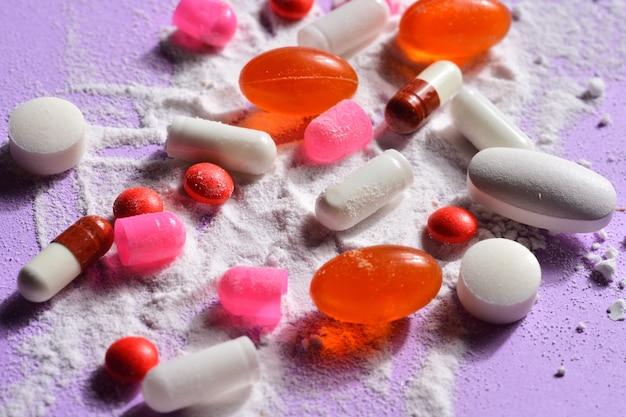 Pílulas de cápsulas quebradas com sua medicação em pó no fundo violeta