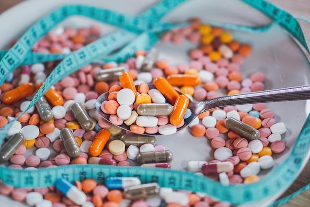 Pílulas de dieta, fita métrica no prato, conceito de conceito de overdose