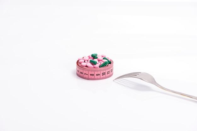 Pílulas de dieta multicoloridas e suplementos, como alimentos em um prato na forma de uma fita de centímetro com um garfo
