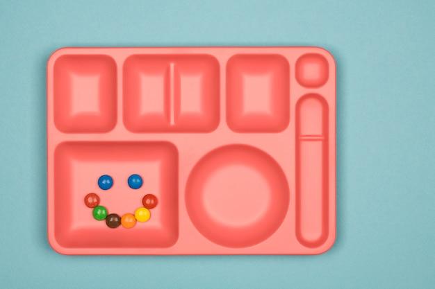 Pílulas de doces de chocolate coloridos na bandeja sobre fundo azul