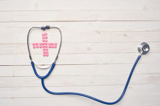 Pílulas de estetoscópio, remédios, tratamento farmacêutico, fundo de madeira