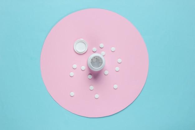 Pílulas de frasco em fundo azul com círculo rosa pastel. vista do topo. natureza morta médica minimalista