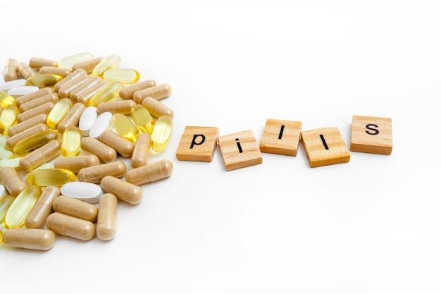 Pílulas de inscrição em cubos de madeira em um fundo branco de diferentes pílulas