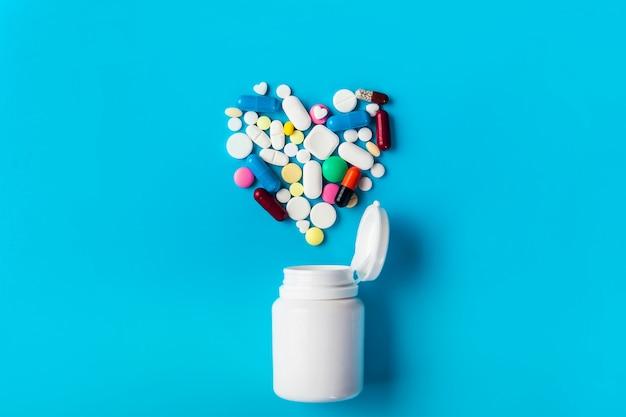 Pílulas de medicamento sortidas, comprimidos e frasco de comprimidos.