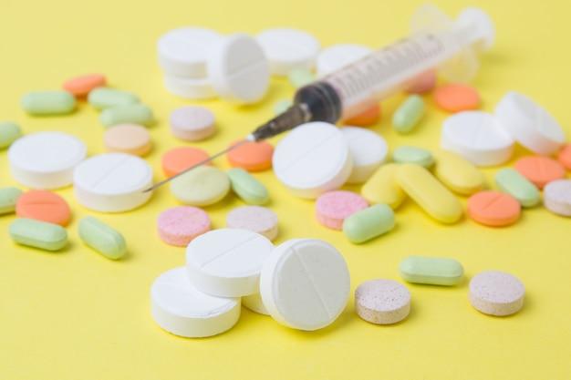 Pílulas de medicamentos, drogas e antibióticos em um fundo amarelo