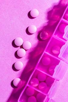 Pílulas de vista superior em fundo rosa