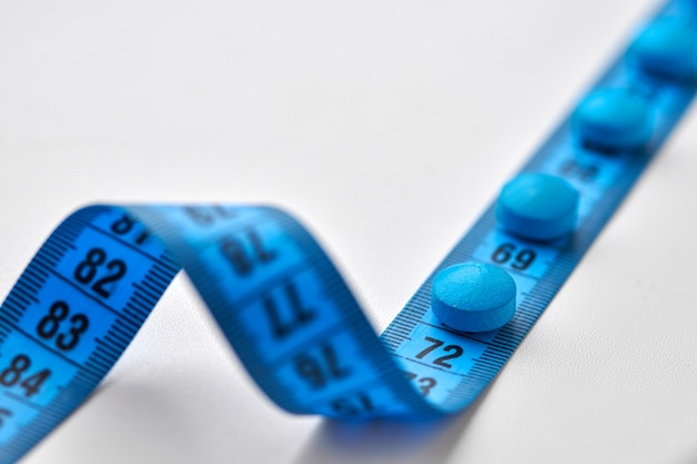 Pílulas dietéticas redondas azuis e fita métrica centimétrica isoladas
