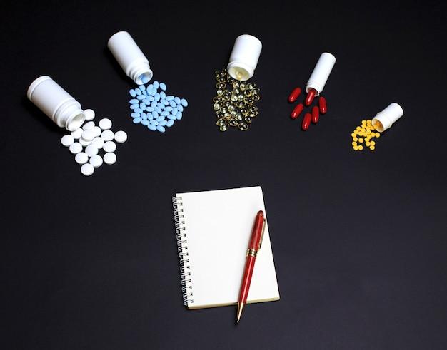 Pílulas diferentes com caderno e lápis preto