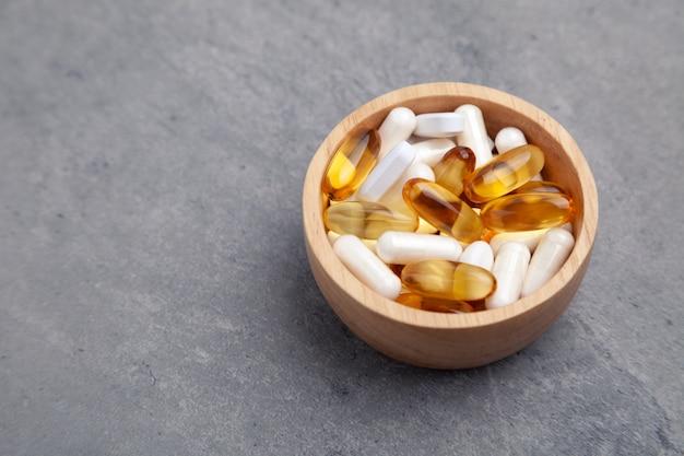 Pílulas diferentes na tigela de madeira