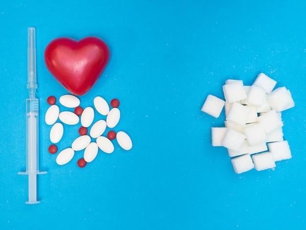 Pílulas drogas coração vermelho e seringa de injeção e blocos brancos de açúcar refinado sobre fundo azul