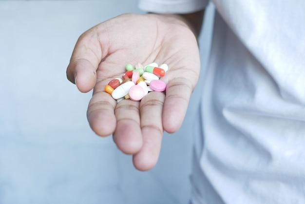 Pílulas médicas multicoloridas e cápsulas na palma da mão