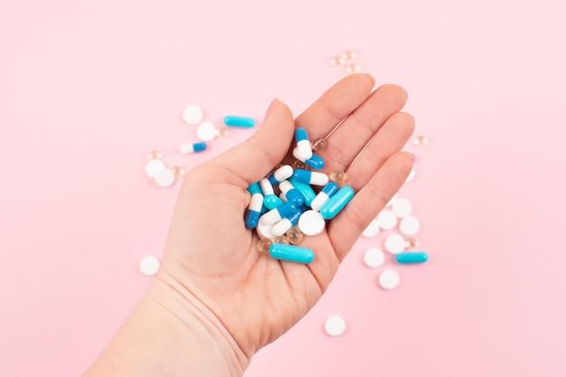 Pílulas multicoloridas brilhantes na mão de mulheres