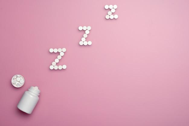 Pílulas soporíferas. medicina do sono com a garrafa branca no fundo cor-de-rosa.