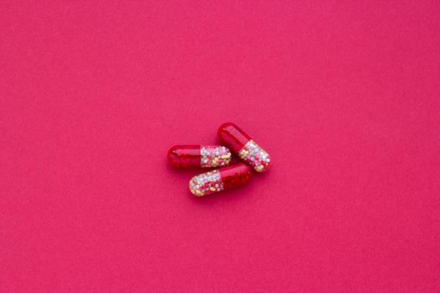 Pílulas vermelhas e amarelas sobre um fundo claret, close-up