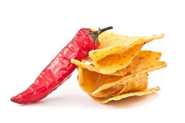Pimenta ao lado de uma pequena pilha de batatas fritas