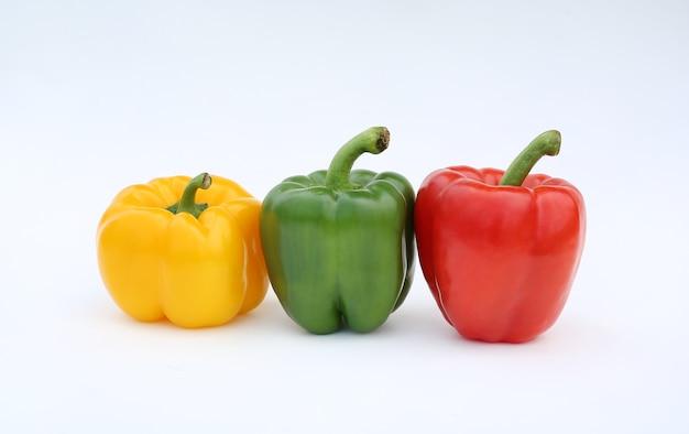 Pimenta de sino verde, vermelho e amarelo isolada no fundo branco.