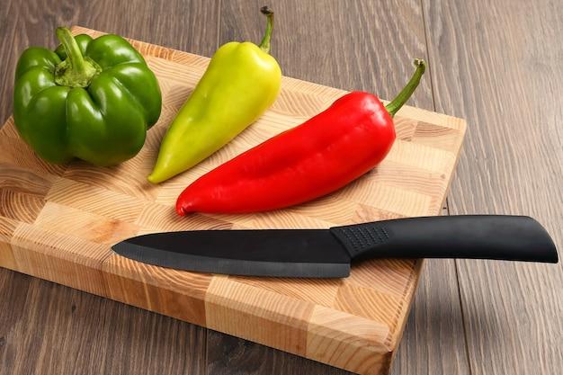 Pimenta doce com faca de cerâmica em uma placa de madeira. alimentos vitamínicos úteis