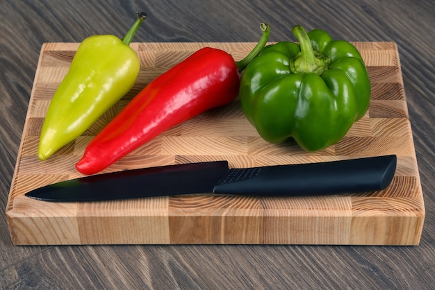 Pimenta doce com faca de cerâmica em uma placa de madeira