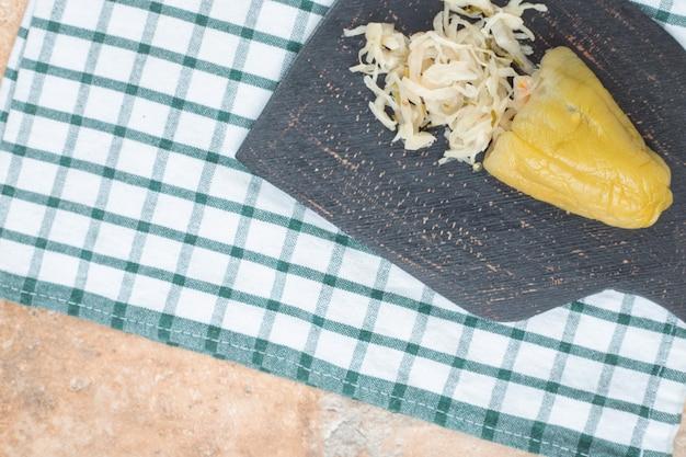Pimenta em conserva recheada com chucrute no tabuleiro escuro.