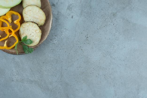 Pimenta fatiada, berinjela e abobrinha na placa de cerâmica.