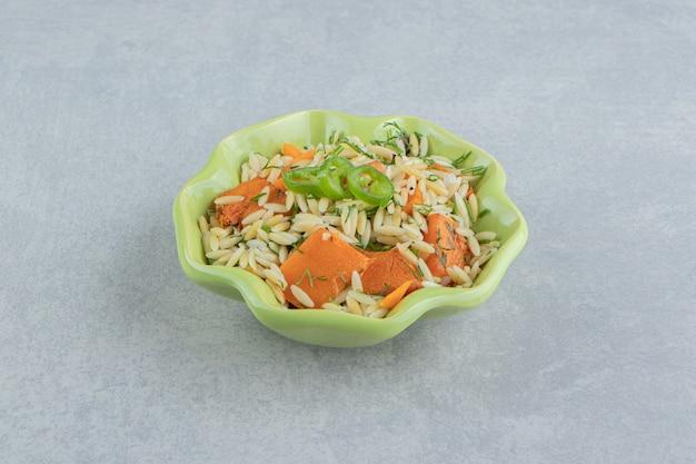 Pimenta fatiada, cenoura com arroz em uma tigela, no fundo de mármore.