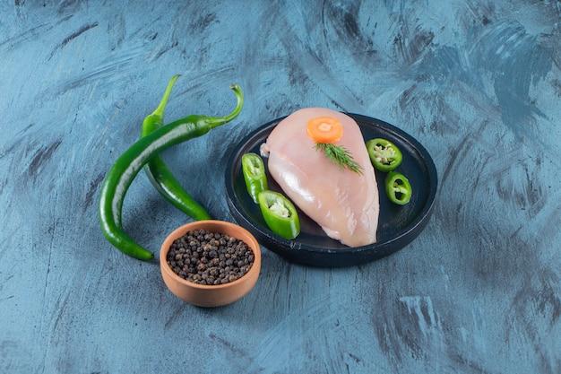 Pimenta fatiada e peito de frango em um prato próximo a uma tigela de temperos, na superfície azul.