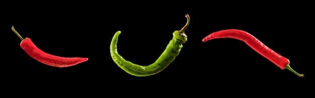 Pimenta jalapeño verde e vermelha em fundo preto.