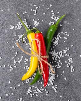 Pimenta malagueta com sal em fundo cinza. vista superior de legumes frescos.