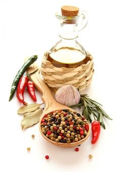 Pimenta na colher de pau, azeite, alho chinês, ervas e especiarias sobre branco