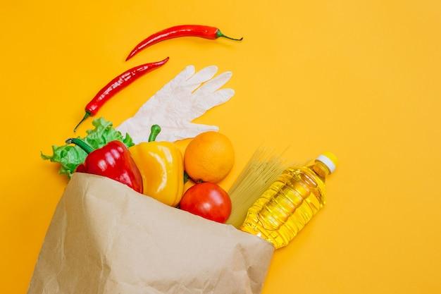 Pimenta, óleo de girassol, tomate, laranja, macarrão, alface em pacote de papel, um conjunto de comida de fazenda vegana em um espaço laranja, frutas e legumes diferentes