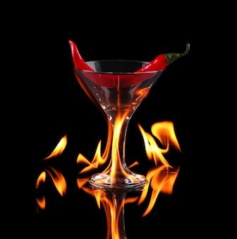 Pimenta picante em uma taça de martini com fogo em um fundo preto