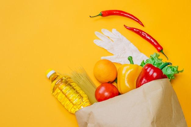Pimenta, pimentão, óleo de girassol, tomate, laranja, macarrão, alface em pacote de papel, um conjunto de comida vegana da fazenda em um espaço laranja