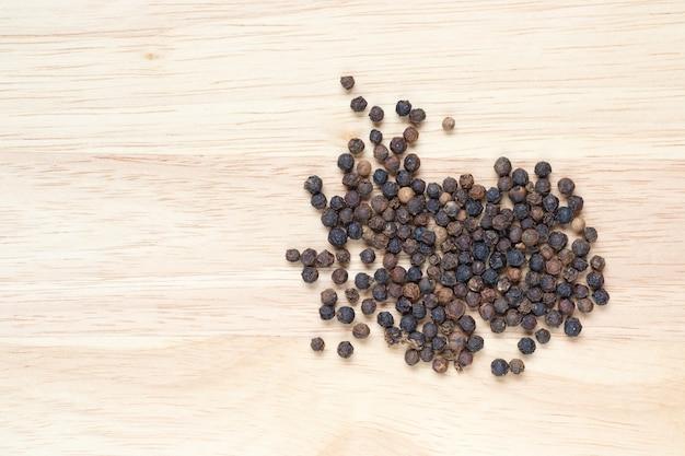 Pimenta preta e cópia espaço na mesa de madeira
