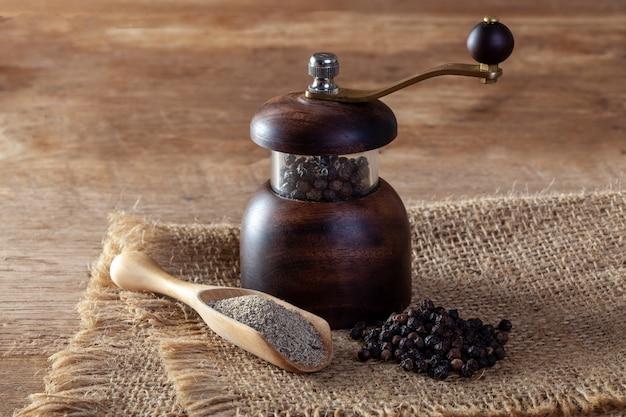 Pimenta preta e moedor de pimenta no chão de madeira