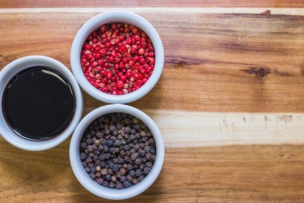 Pimenta preta e vermelha, soja na mesa de madeira
