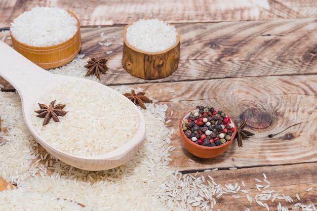 Pimenta preta fresca e anis estrelado com arroz cru sobre a mesa de madeira