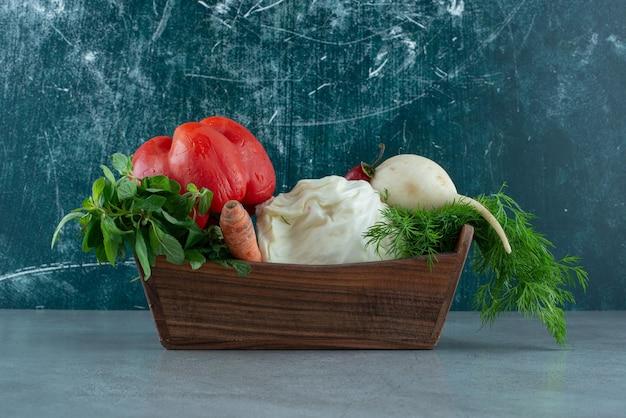 Pimenta, rabanete branco e verduras em caixa de madeira.