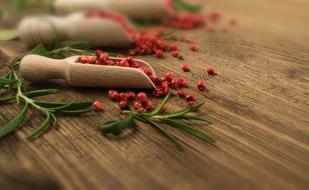 Pimenta rosa ou grãos de pimenta vermelha na mesa de madeira. sementes secas de schinus com alecrim fresco em mesa rústica de madeira