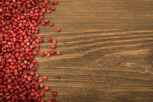 Pimenta rosa ou grãos de pimenta vermelha na mesa de madeira. sementes secas schinus