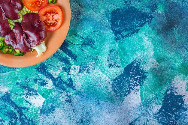 Pimenta, tomate, alface e vísceras de frango em um prato de barro