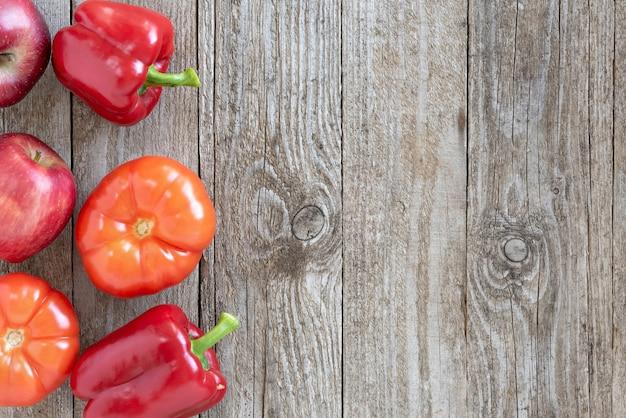 Pimenta, tomate e maçã em um fundo de madeira.