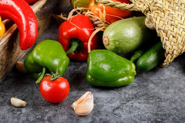 Pimenta, tomate e outros vegetais fora de uma cesta.