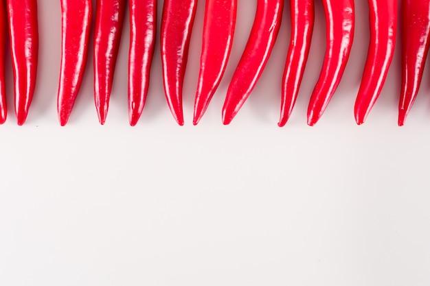 Pimenta vermelha acima do quadro na superfície branca com espaço de cópia