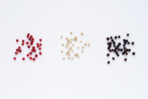 Pimenta vermelha, branca e preta em branco