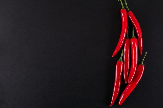 Pimenta vermelha com espaço de cópia na vista superior de superfície preta